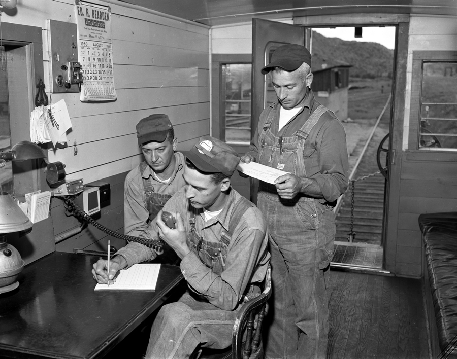 4x5 Negative Box: AUD 0027 Prints Box: Pueblo Plant Sub 0001-0134 Numbered SUB 0079 Date: 08/31/1960 Three workers using new radio communications on C&W Railroad at Segundo Colorado.